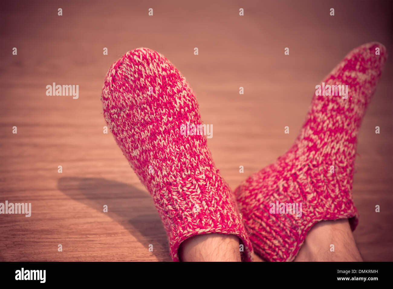 Man Legs in red Wool Socks male knitted clothes winter handmade accessories home comfort concept on wooden background trendy - Stock Image