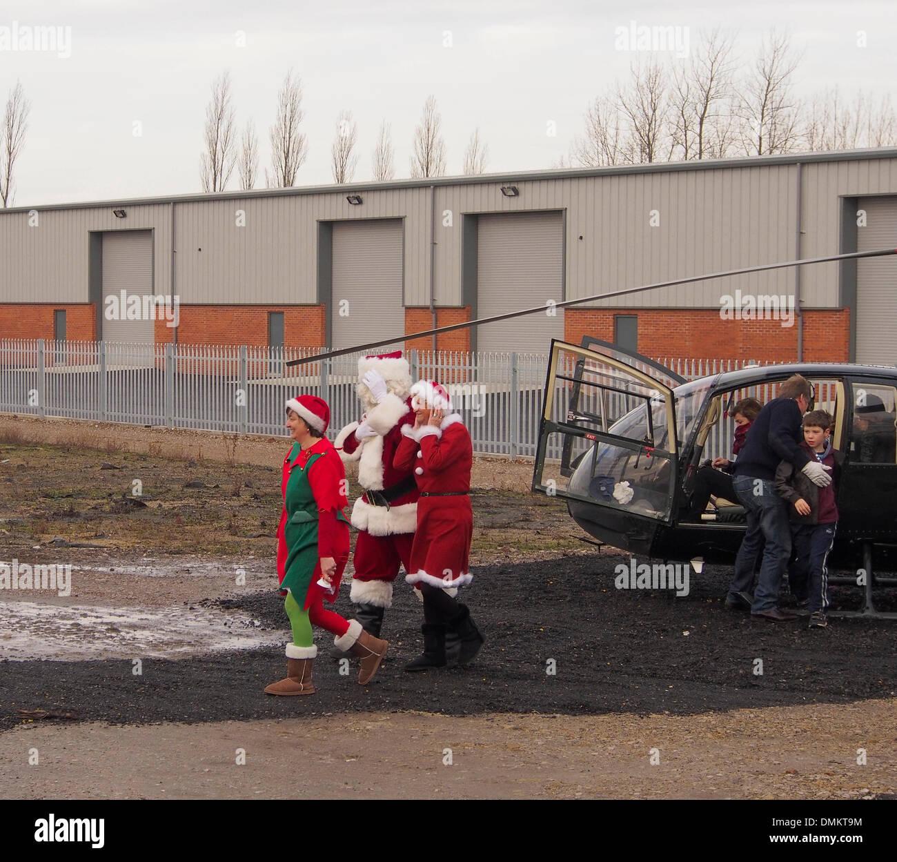 Leyland, Preston, Lancashire, UK. 15th Dec 2013. Santas elves escorting Santa to meet the children and parents awaiting his arrival. Credit:  Sue Burton/Alamy Live News - Stock Image