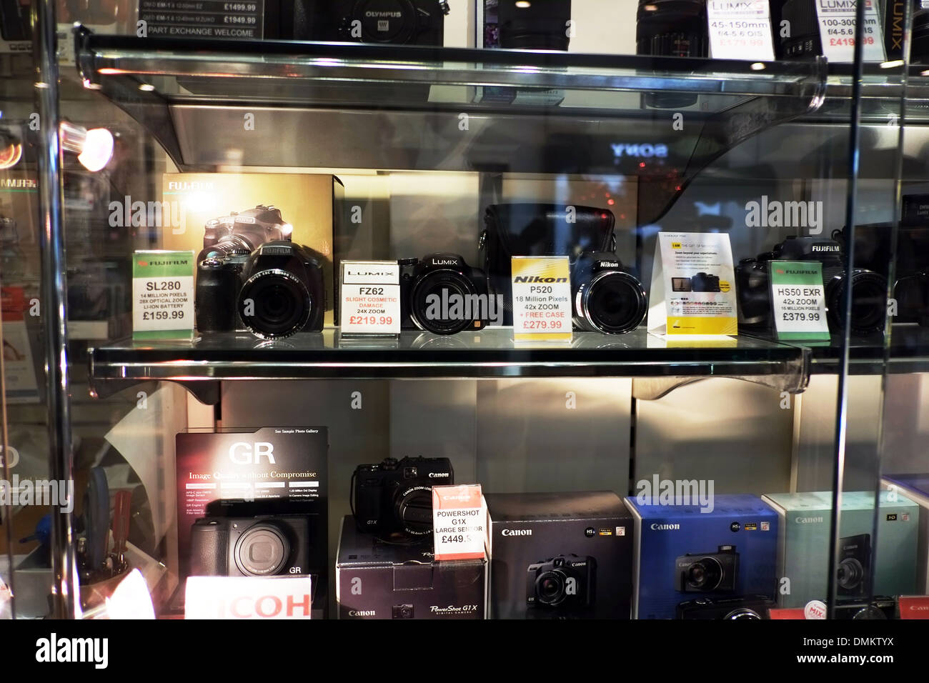 Fuji canon nikon camera display cabinet in shop new cameras for sale in glass case cabinet lens lenses displayed - Stock Image