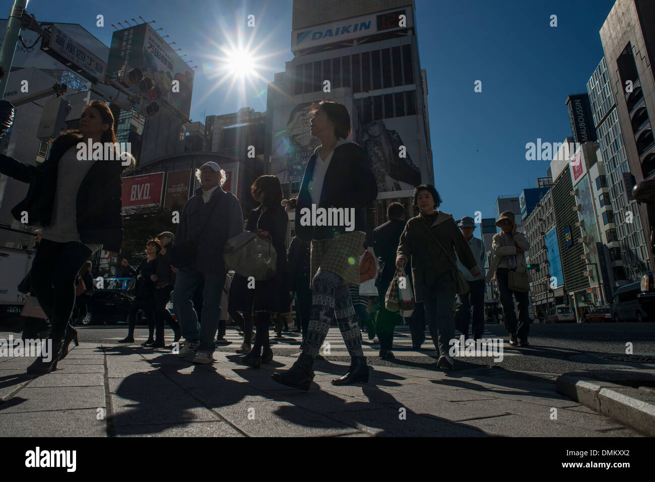 Pedestrians cross the road in Shinjuku, a major high end shopping district in Tokyo, Japan. Stock Photo