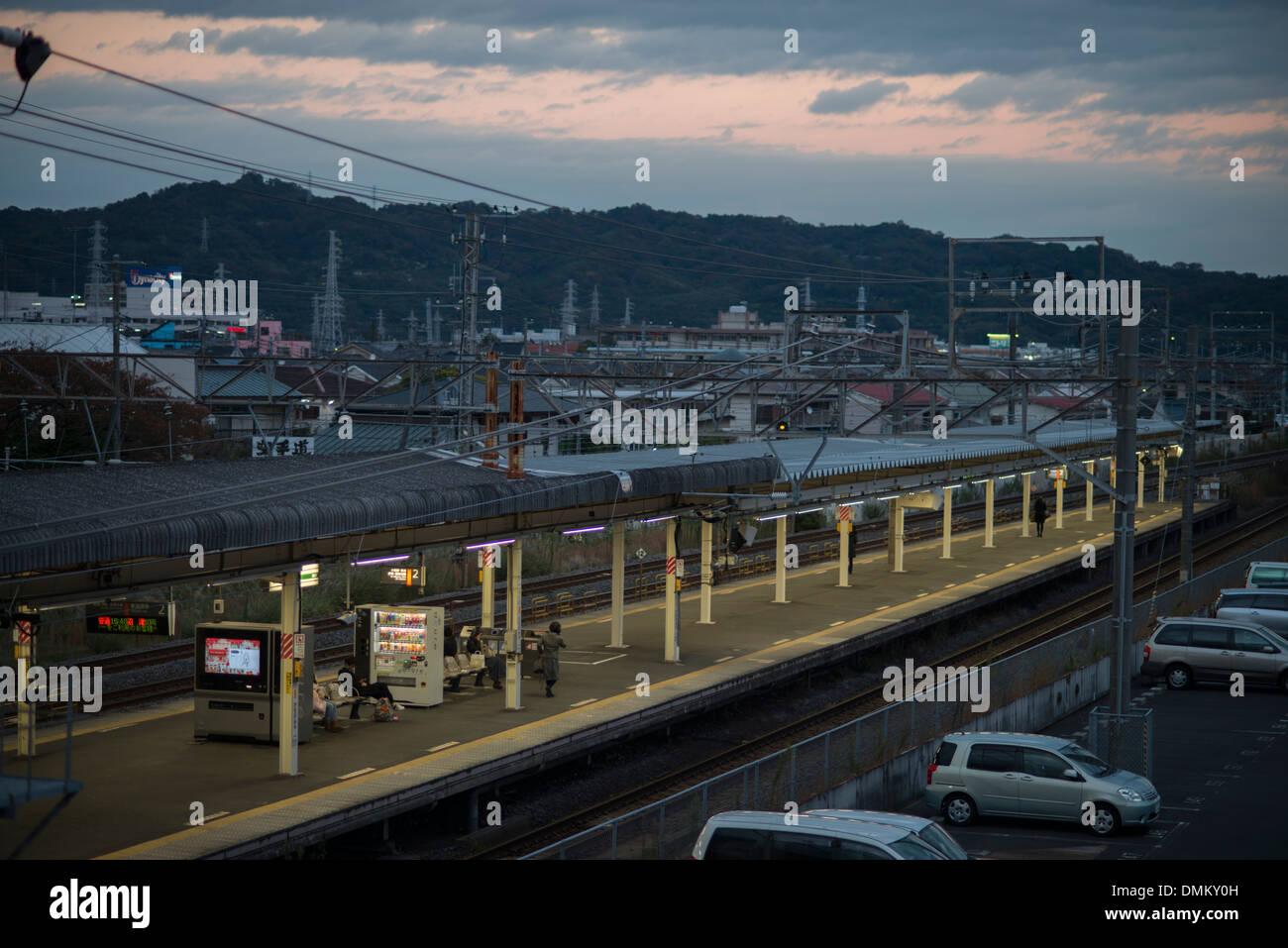 PAssengers await a train as the sun rises behind Odawara train station,  Kanagawa Prefecture, Tokyo, Japan - Stock Image