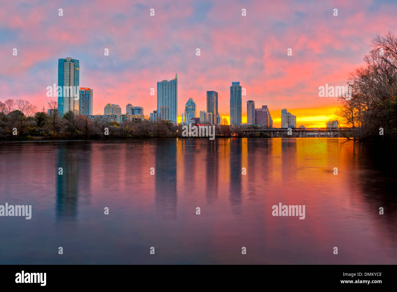 The Austin skyline is reflected in the waters of Lady Bird Lake on an early morning sunrise. - Stock Image