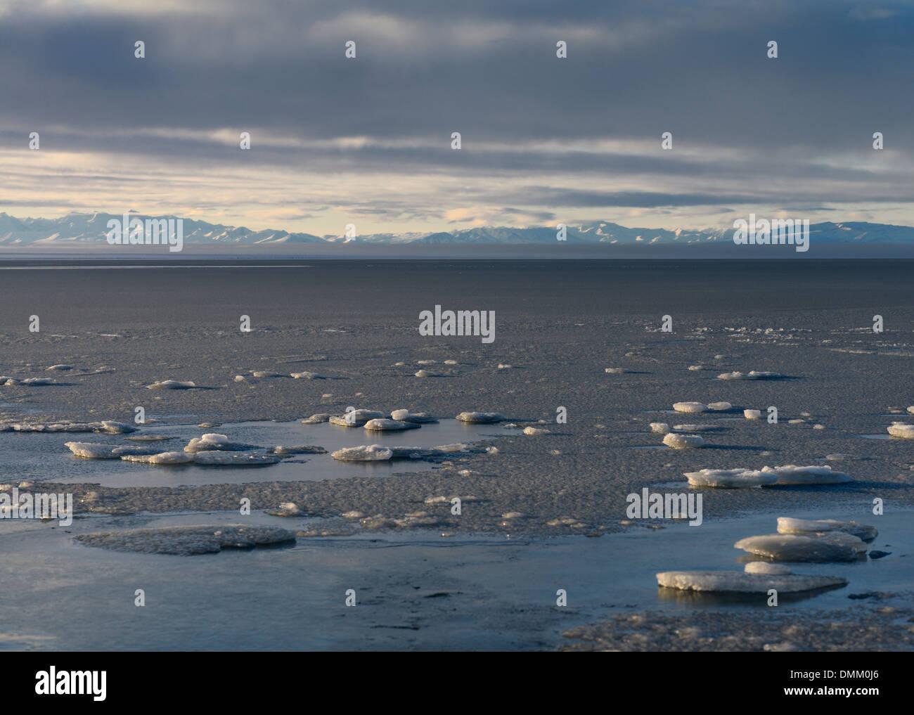 Broken Ice on frozen Kaktovik Lagoon Alaska USA with Brooks Range mountains at the Beaufort Sea Arctic Ocean - Stock Image