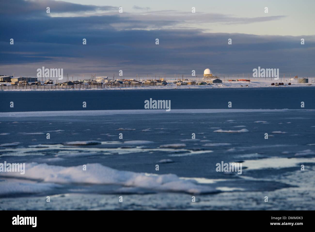 Ice and snow on Kaktovik lagoon with Eskimo homes and DEW line station on Barter Island Alaska USA on the Beaufort Sea Arctic Ocean - Stock Image
