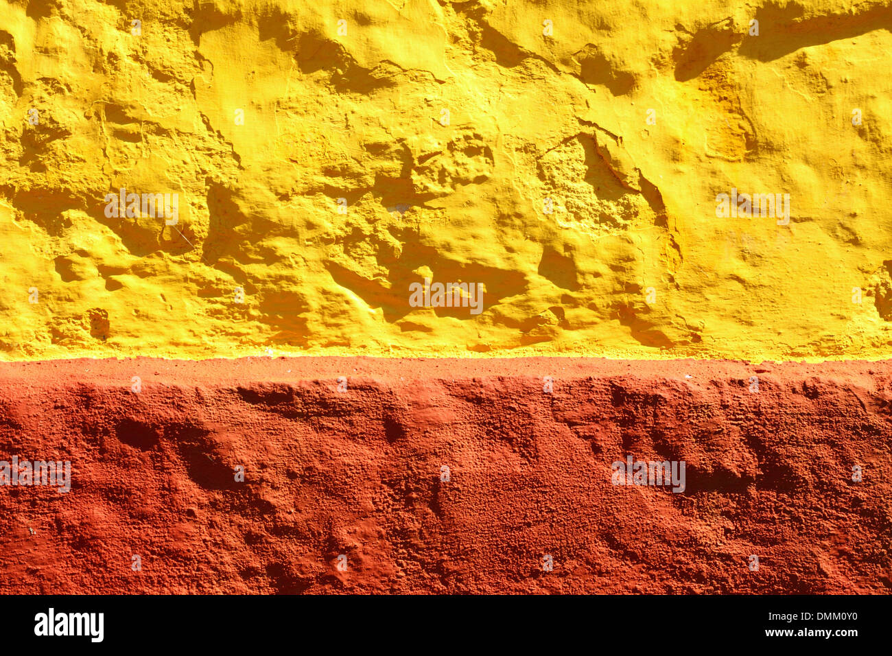 close up yellow red paint uneven rough old concrete wall