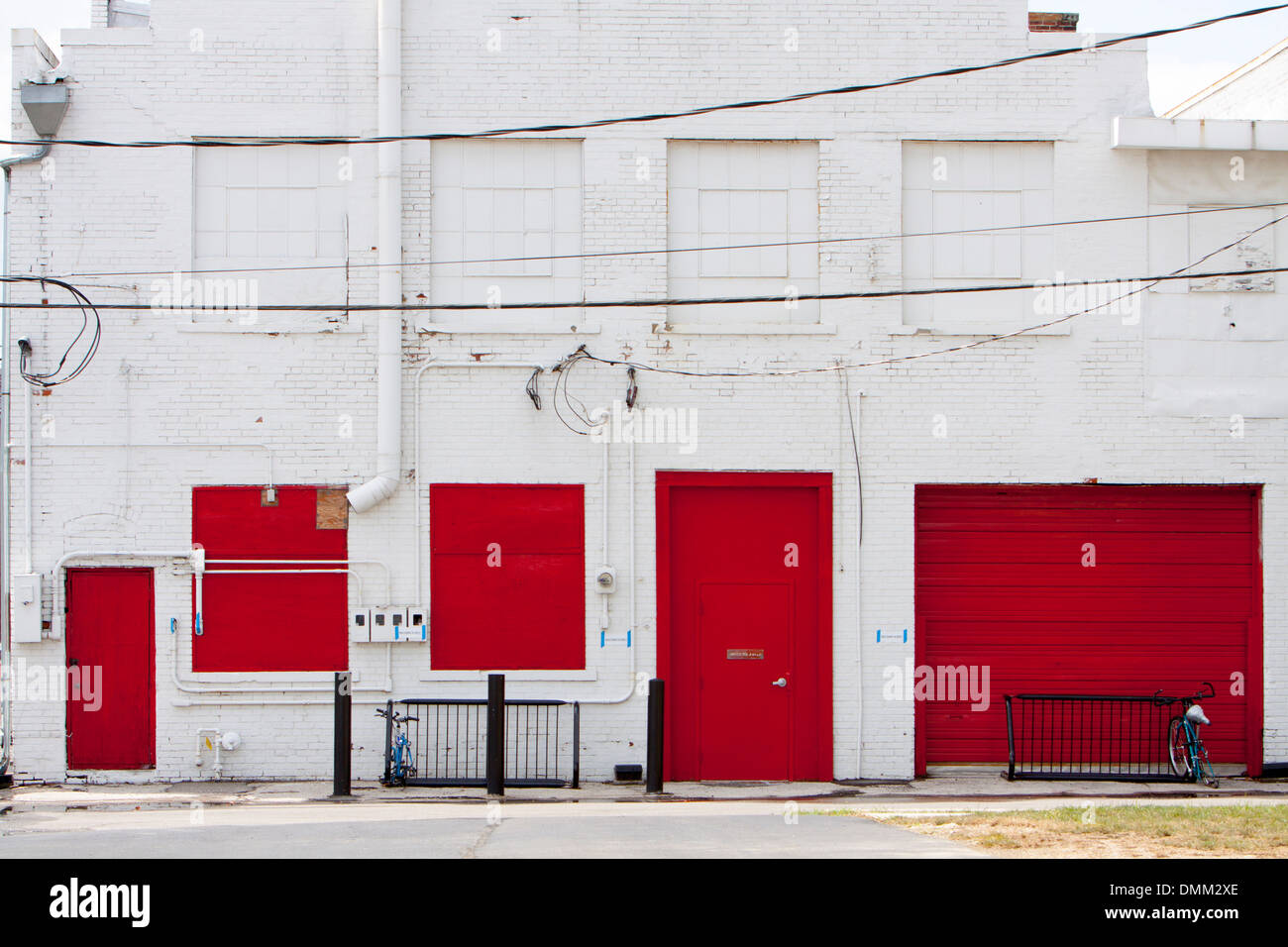 Red doors and windows in the back of a white building in Columbus, Ohio, USA. - Stock Image