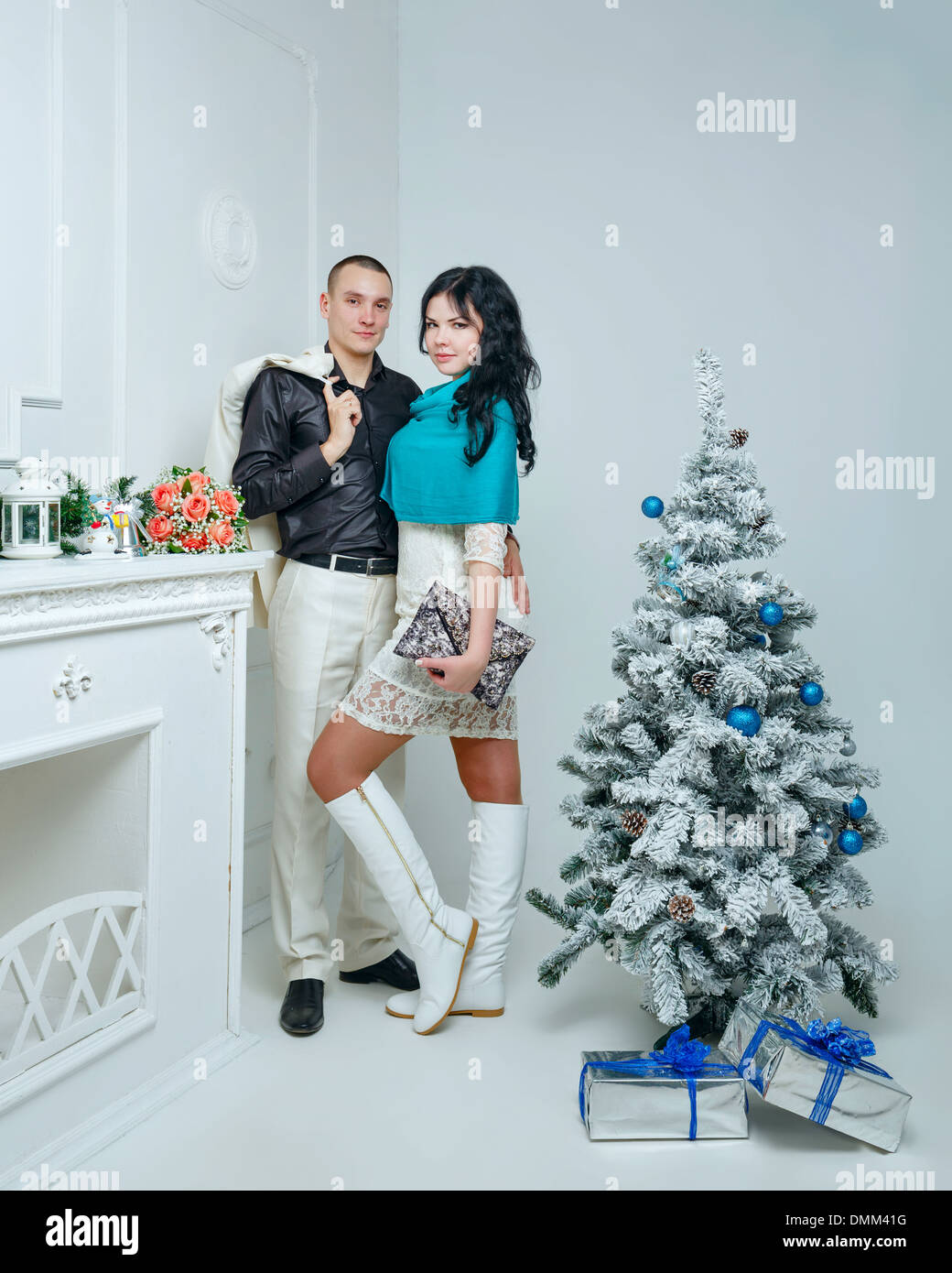 young loving married couple near christmas tree with gifts stock image