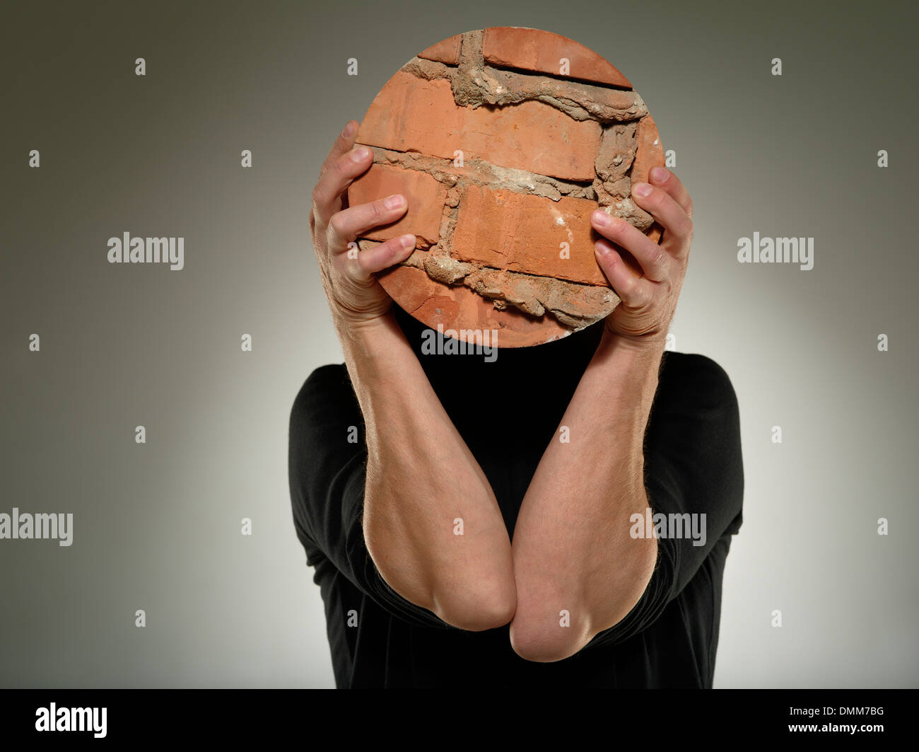 Man hold on piece of rounded brick wall over his face. Obsession  concept. - Stock Image
