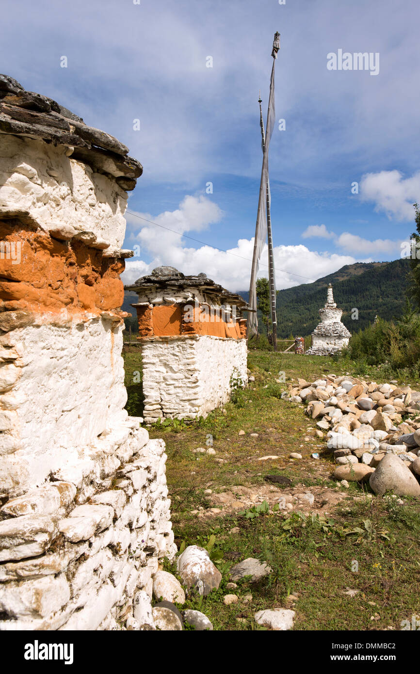 Bhutan, Bumthang Valley, Jambey old coarsely painted mani wall and stone chorten - Stock Image