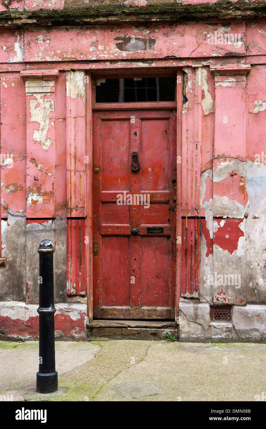 Front door of a peeling and dilapidated looking house in Princelet Street, Spitalfields. - Stock Image