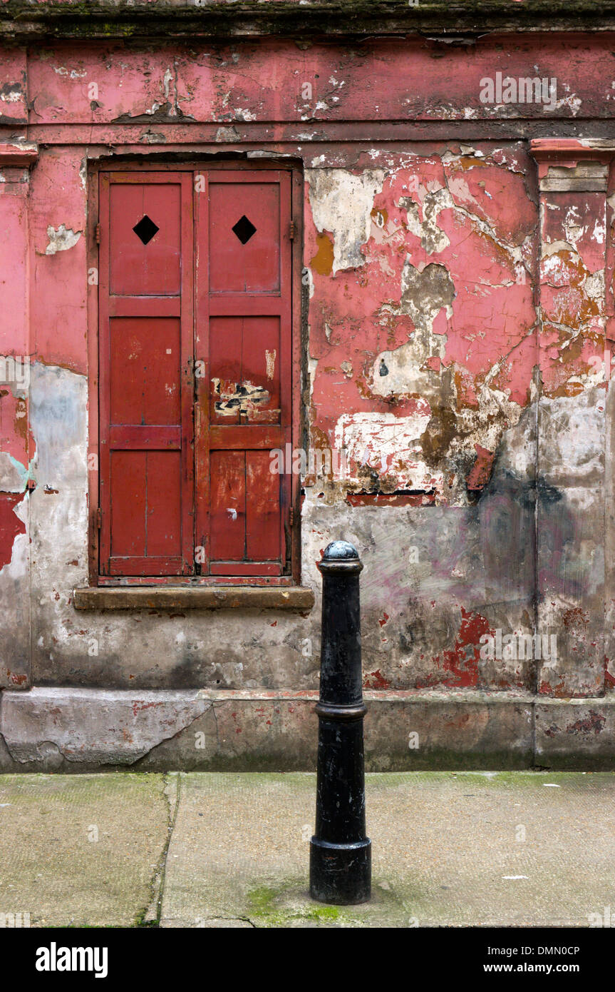Window and shutters of a peeling and dilapidated looking house in Princelet Street, Spitalfields. - Stock Image