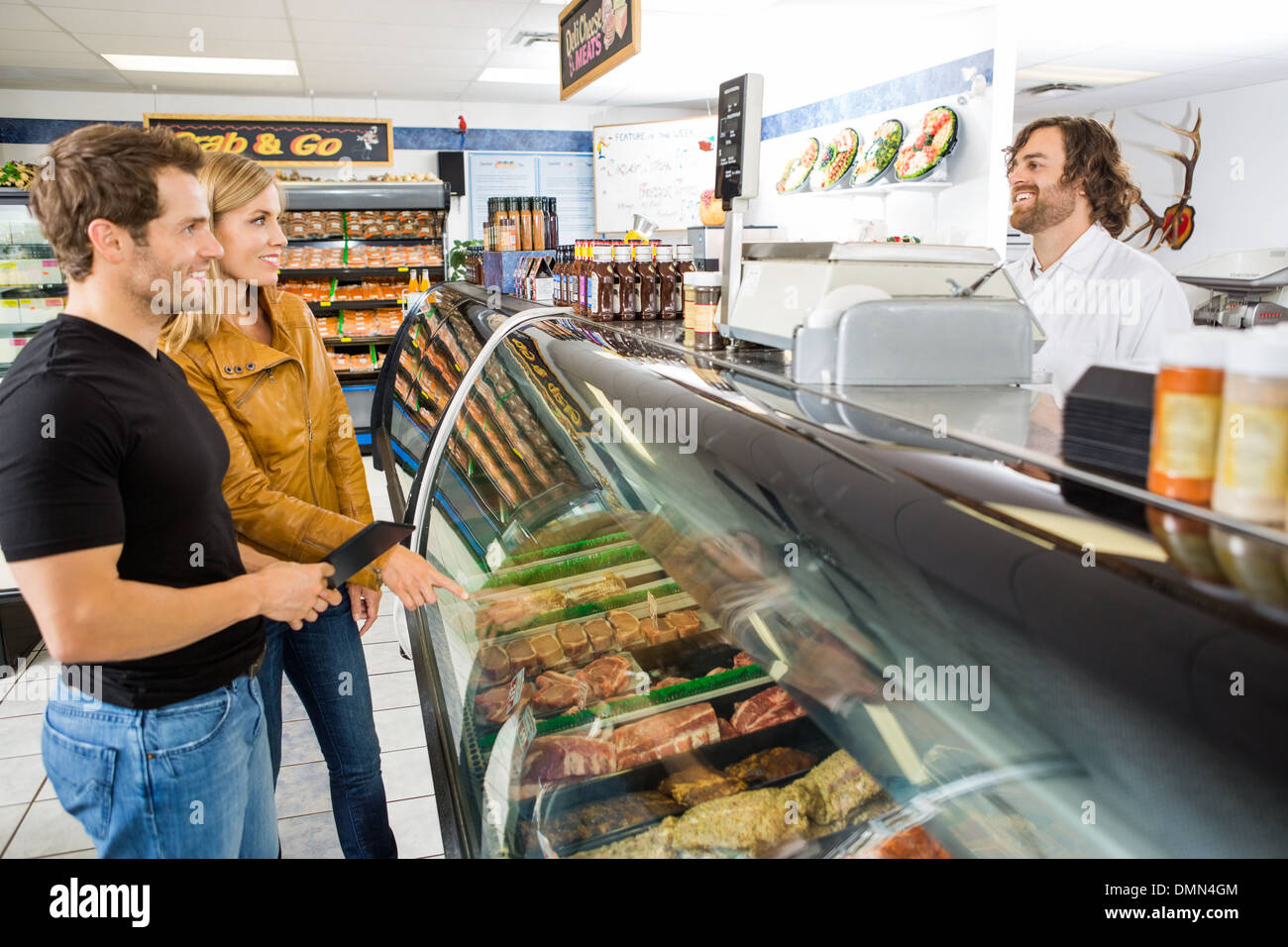 Salesman Attending Customers At Butcher's Shop Stock Photo