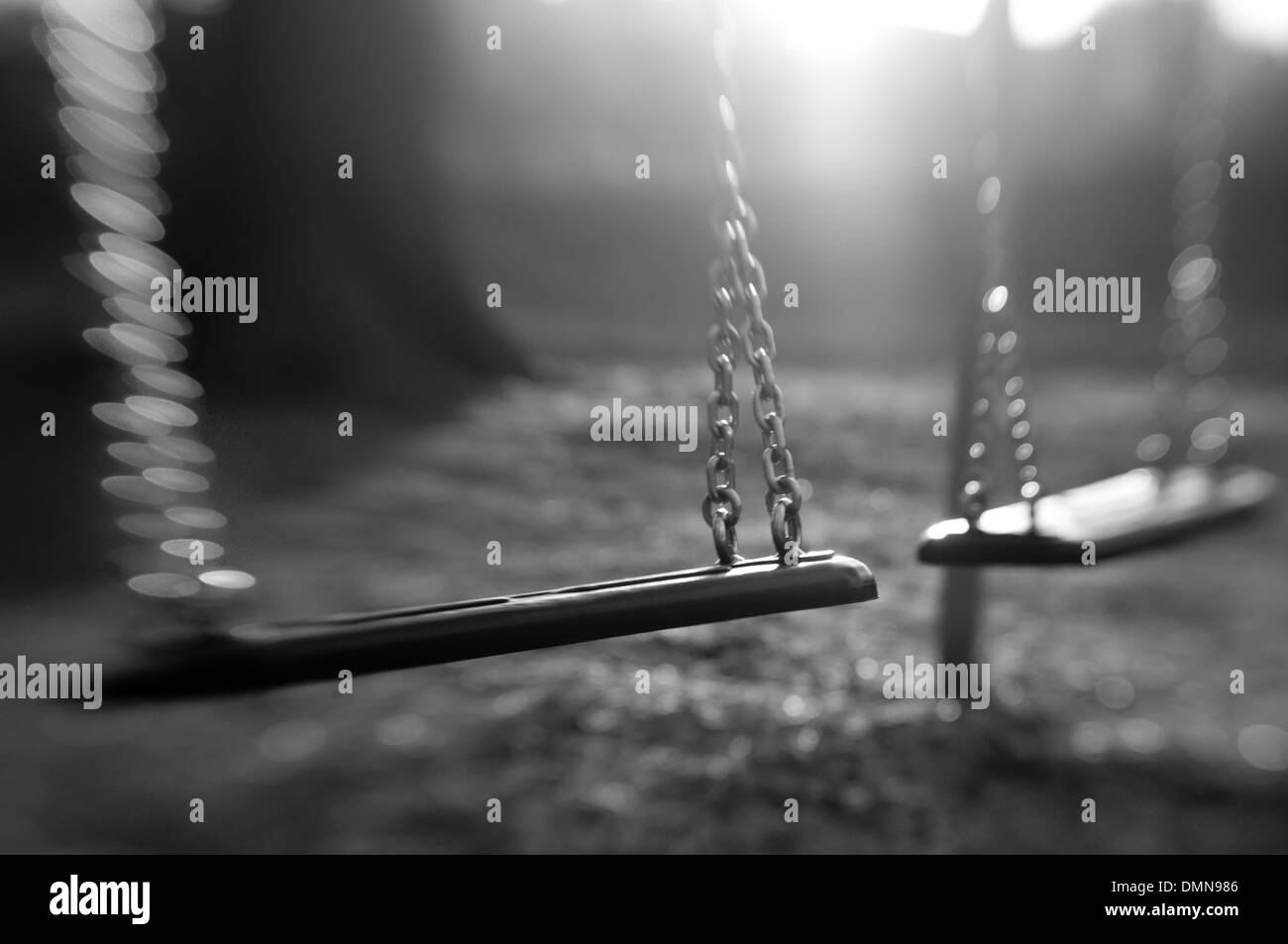 Abandoned swings on a playground - Stock Image
