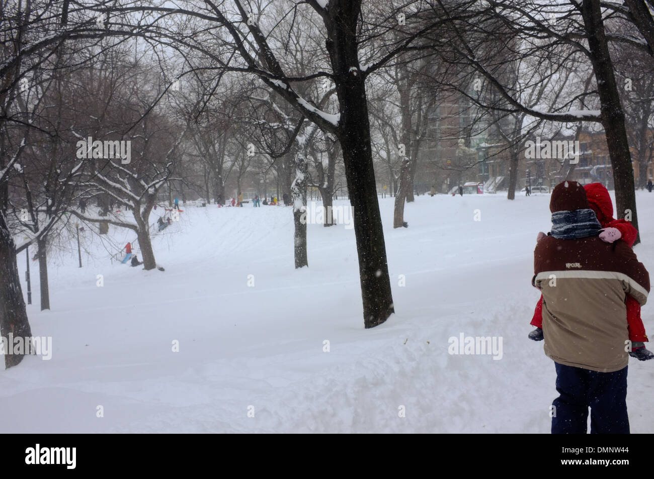 A father carries his daughter through a snow covered Parc Lafontaine in Montreal, Quebec - Stock Image