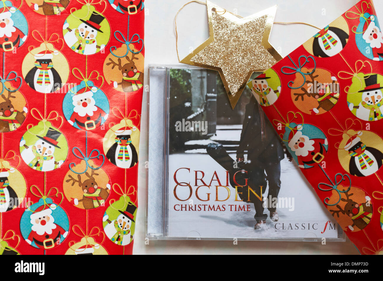 Christmas wrapping paper to wrap Craig Ogden Christmas Time CD compact disc as a present - Stock Image