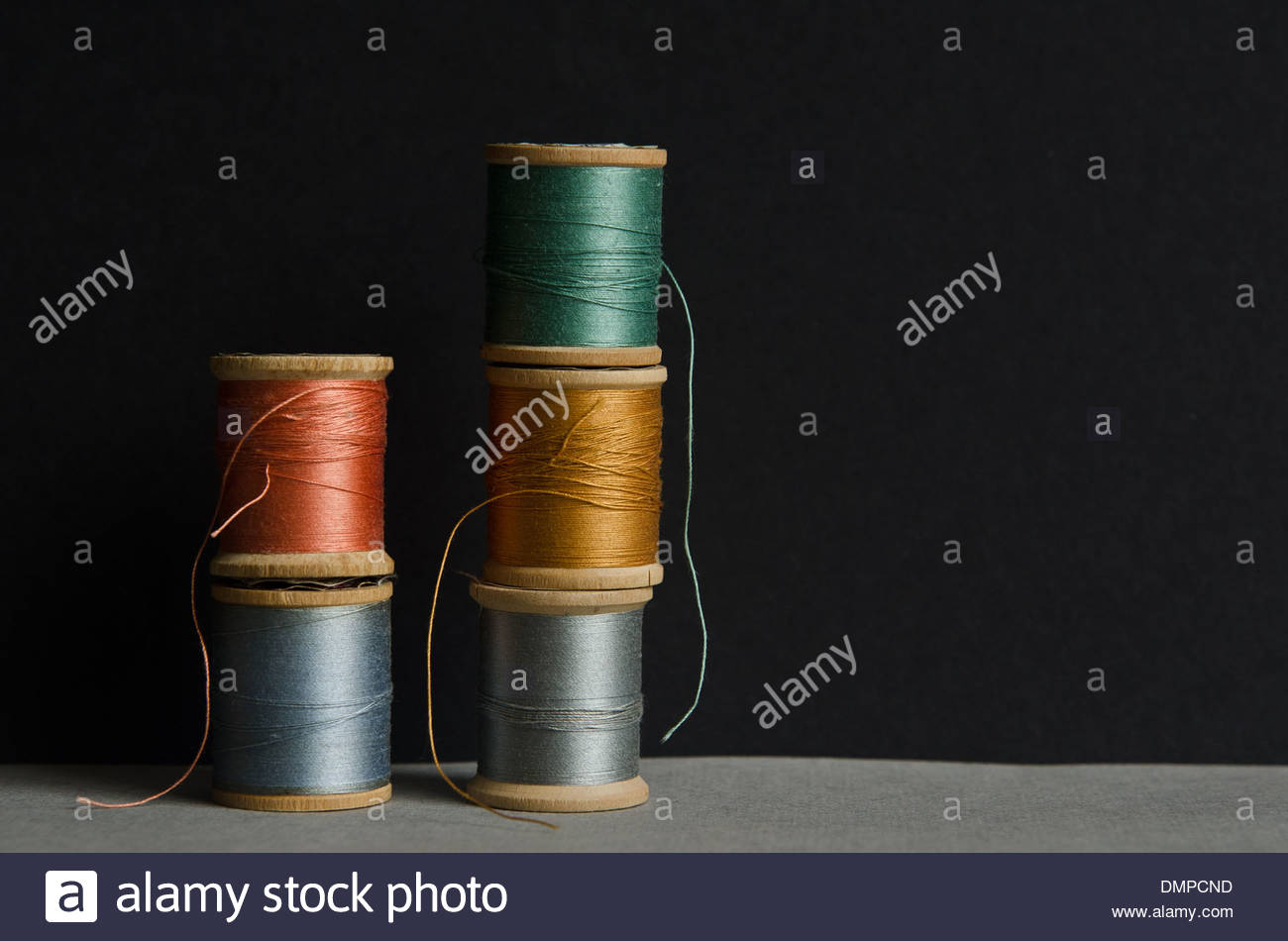 Wooden spools of colored thread stacked together with black background. - Stock Image