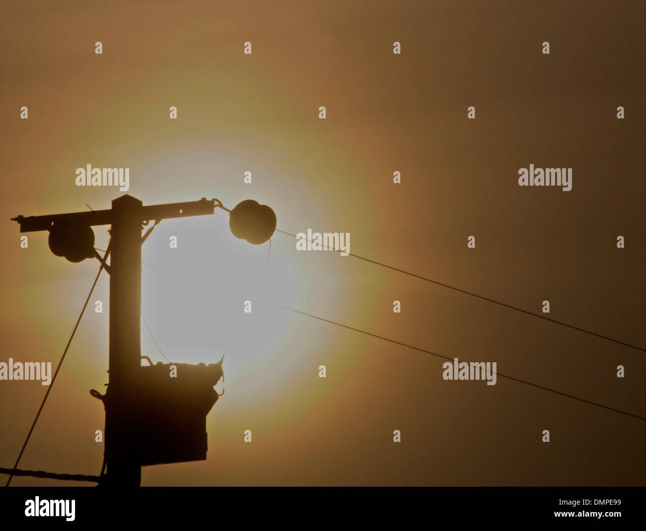 Electric pole sunset energy crisis - Stock Image