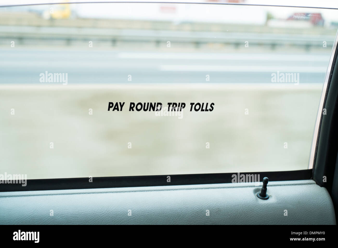 Detail shot of New York yellow taxi showing the window sign saying Pay Round Trip Tolls. - Stock Image