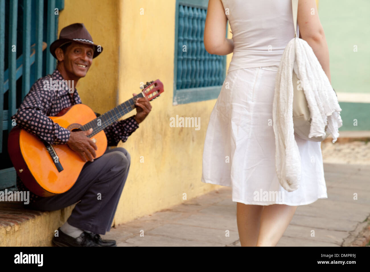 A  guitarist playing in this street scene as a woman walks past - Cuban culture in Trinidad, Cuba, Caribbean, Latin America - Stock Image