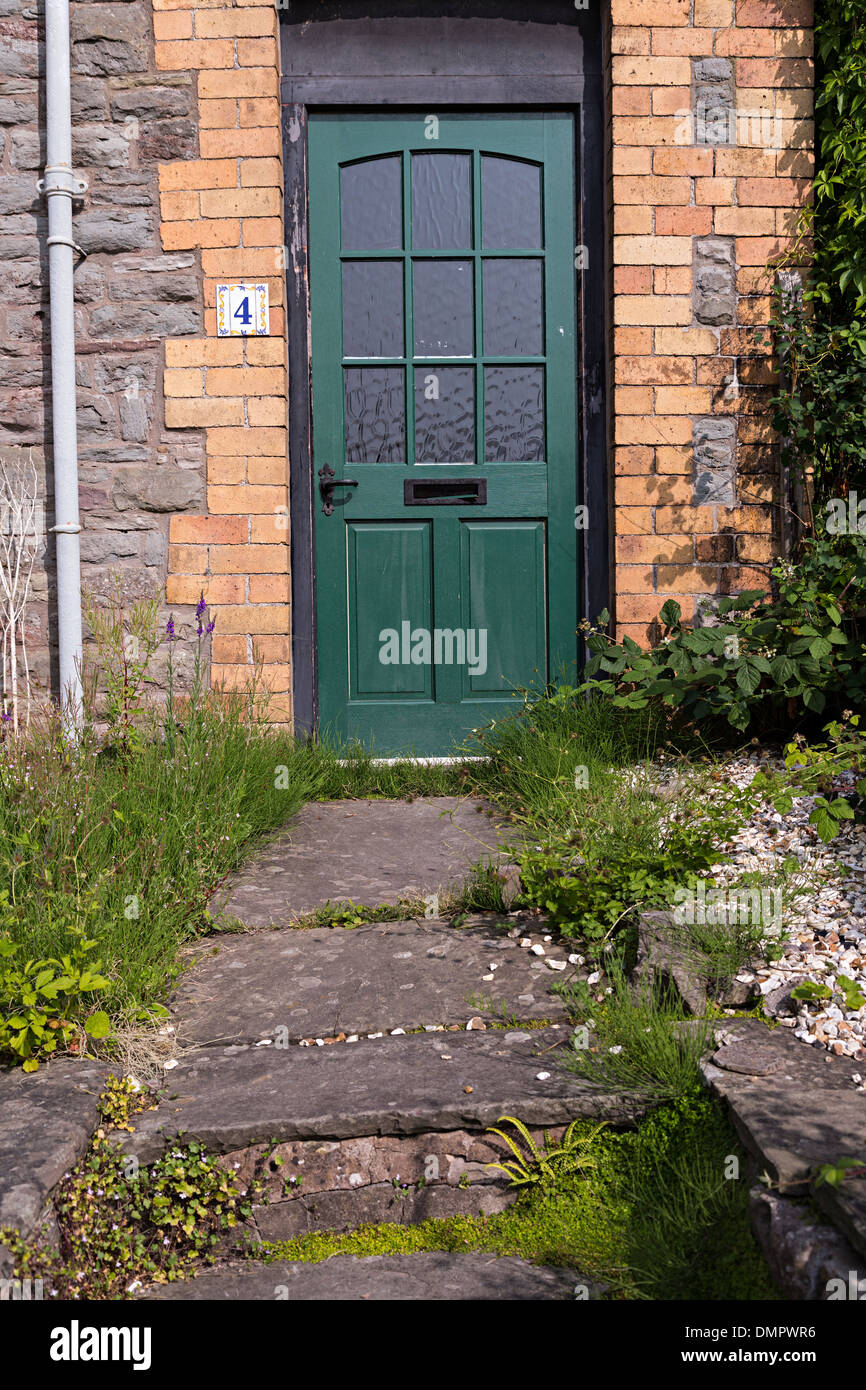Green Front Door To House With Number 4 And Overgrown Stone Path, Hay On Wye