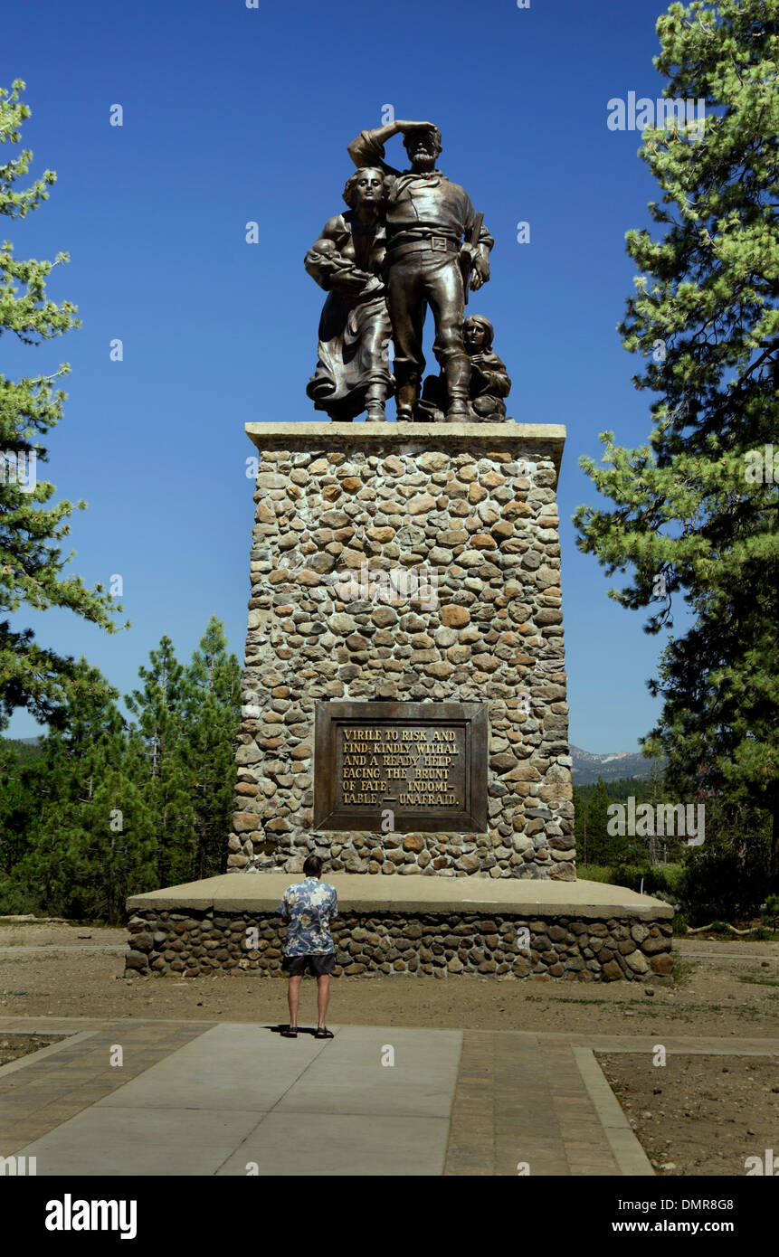 Man stands in front of Donner Pass monument, Statue of father, mother, young boy and baby on top of stone pedestal - Stock Image