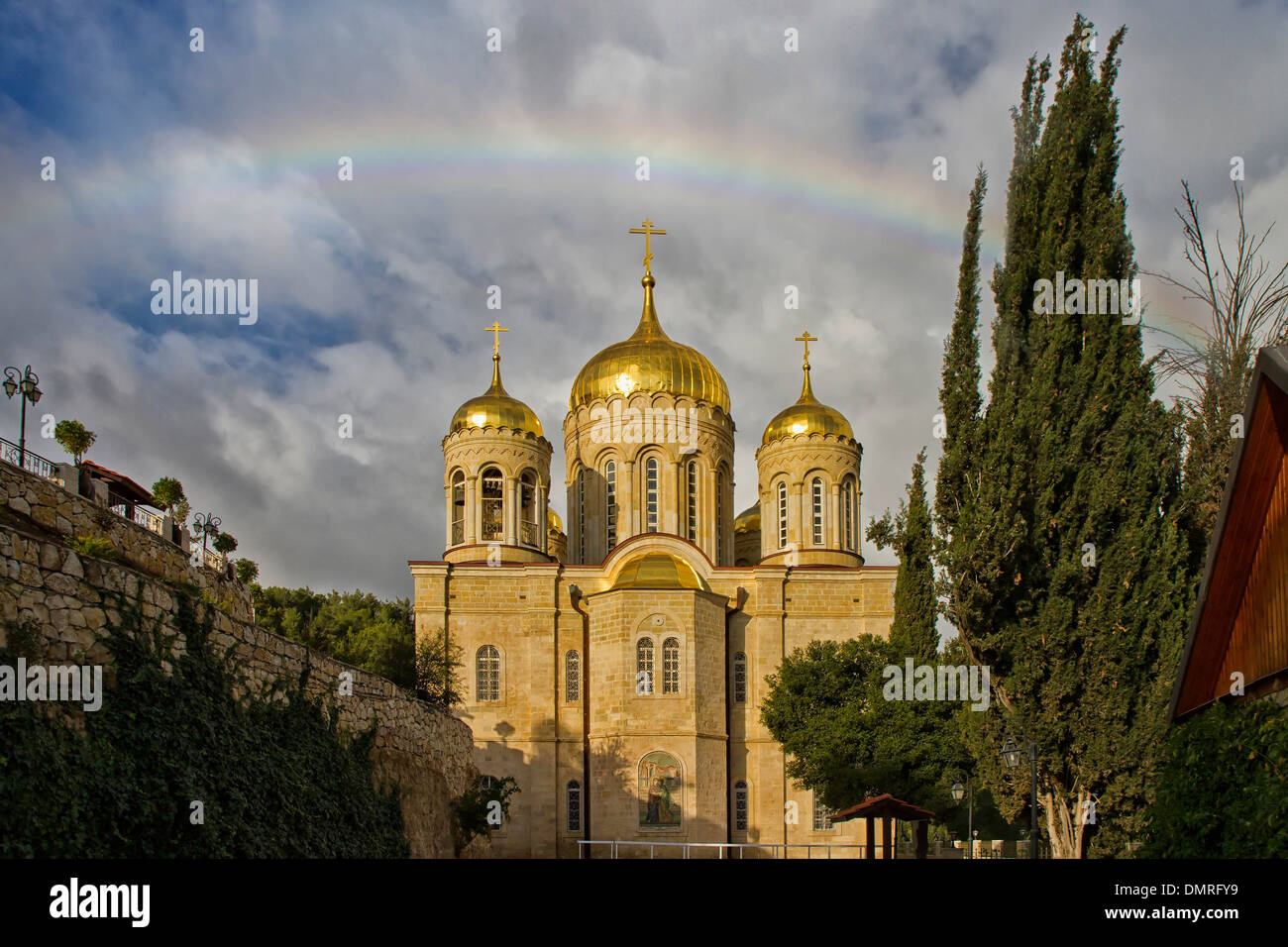 A rainbow breaks over the golden domes of Gornensky monastery of the Russian Ecclesiastical Mission in Jerusalem. - Stock Image