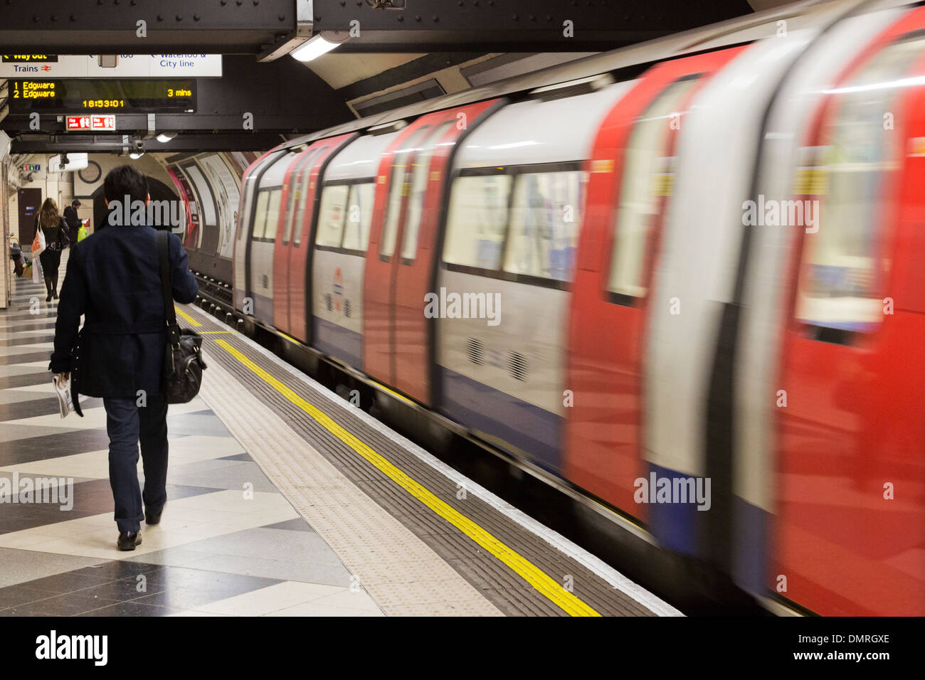 Person walking down the platform on a London Underground tube station. - Stock Image