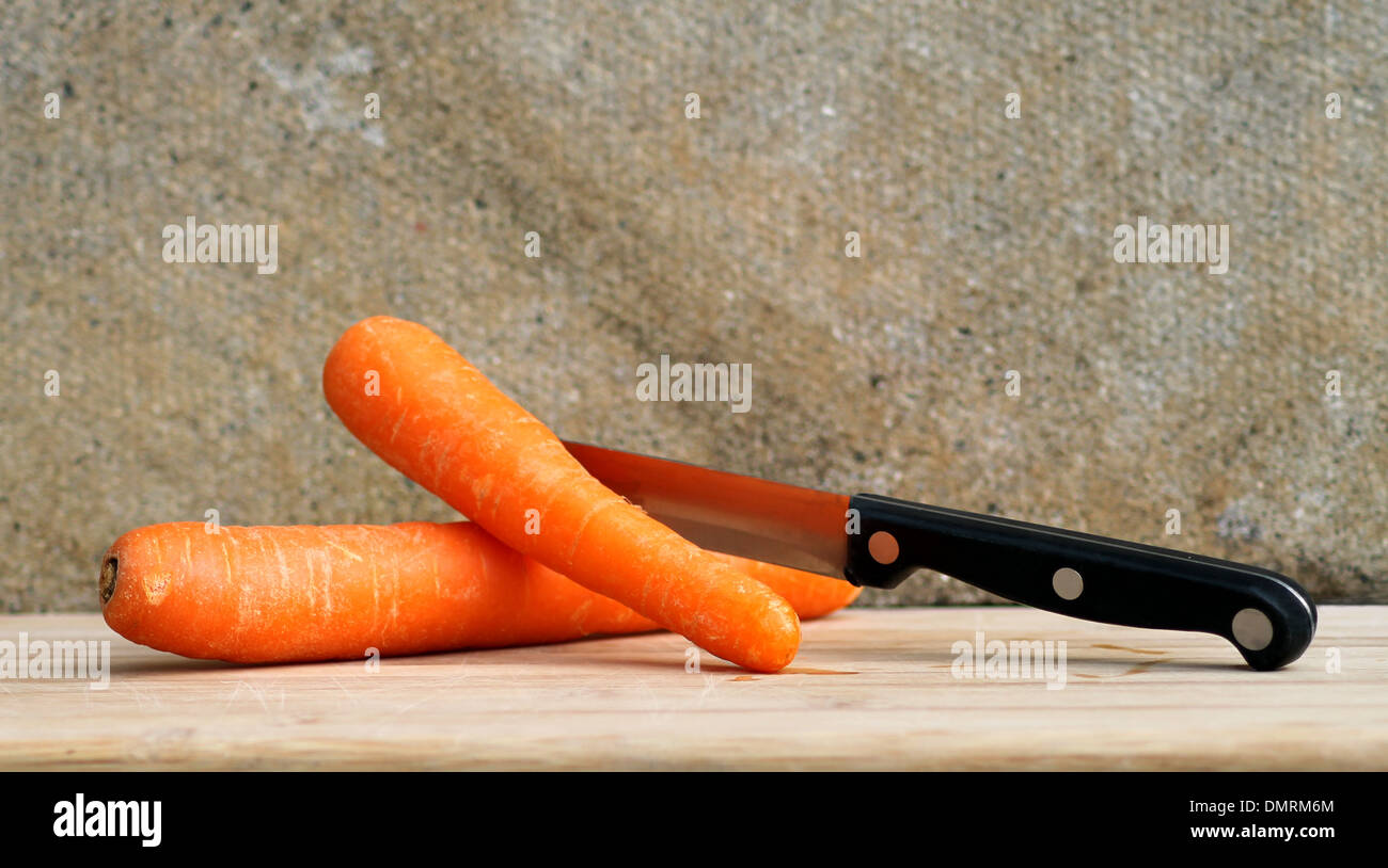 Fresh carrots and kitchen knife on wooden cutting board. - Stock Image