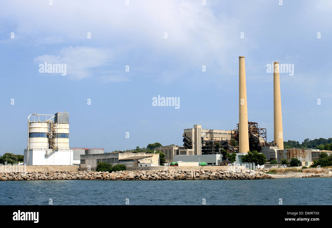 Industrial factory with tall chimney view from ocean. - Stock Image