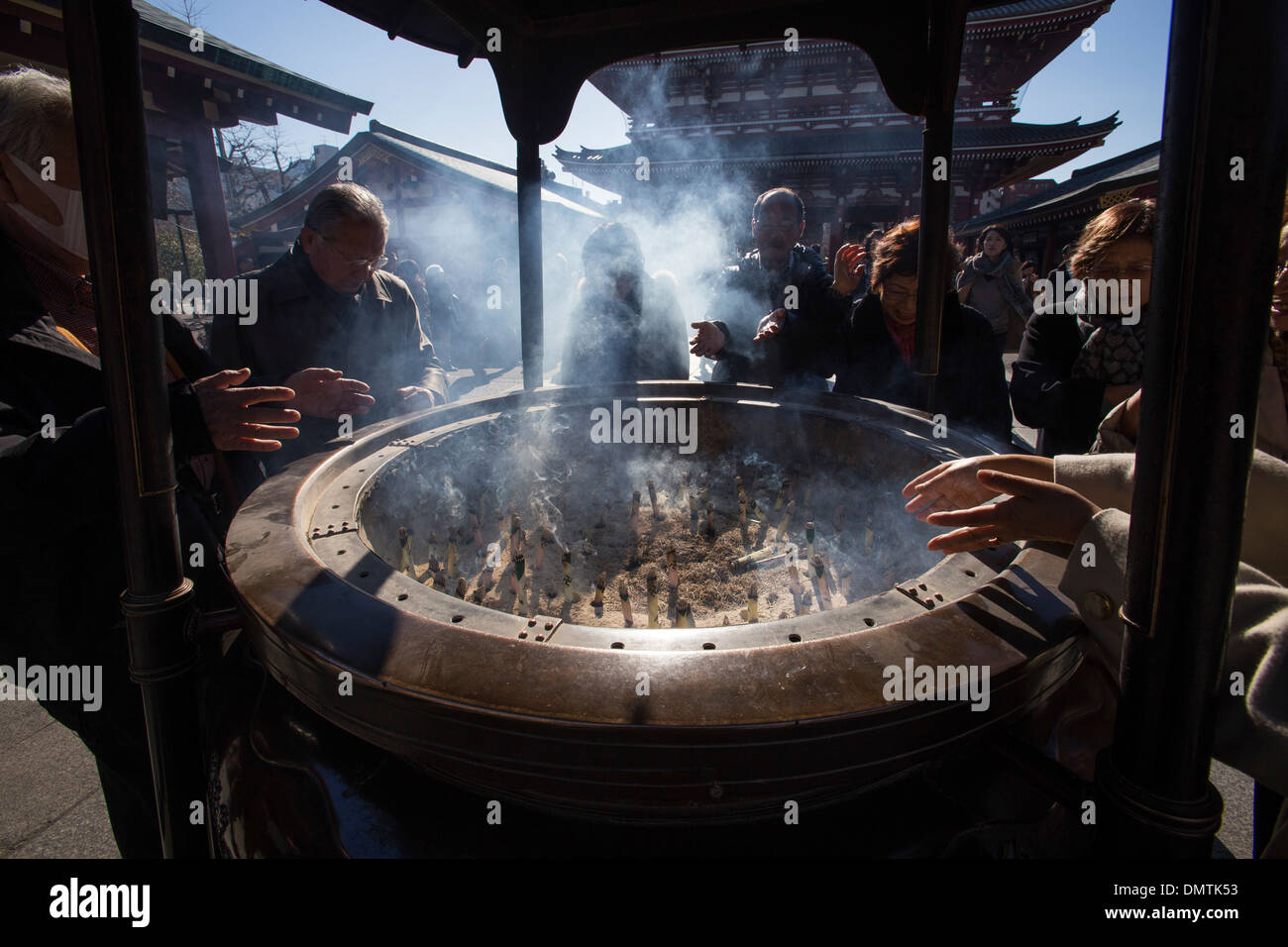 At Sensoji Japanese direct the smoke from incense over themselves especially to areas that need healing. - Stock Image