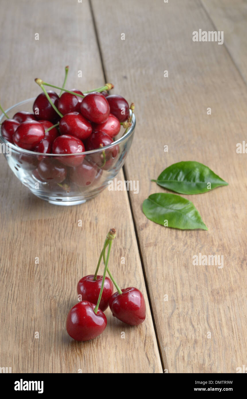 Bowl of organic Cherries on wooden table - Stock Image