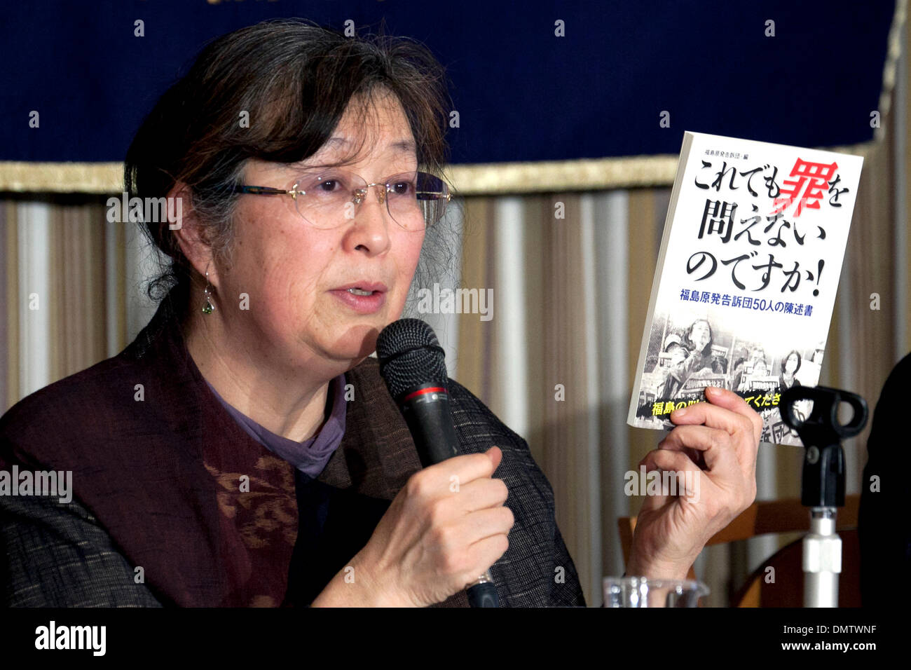 Tokyo, Japan. 17th December 2013. - Representative of Fukushima Disaster Plaintiffs, Ruiko Mutoh shows the book Do You Still Say 'No Criminals Changes'! Statements by 50 Members of The Complainants for the Criminal Prosecution of the Fukushima Nuclear Disaster at the Foreign Correspondents' Club of Japan (FCCJ). Mutoh speaks about the legal process of the suit against 32 former, current executives of TEPCO and the corporation. Credit:  Aflo Co. Ltd./Alamy Live News - Stock Image