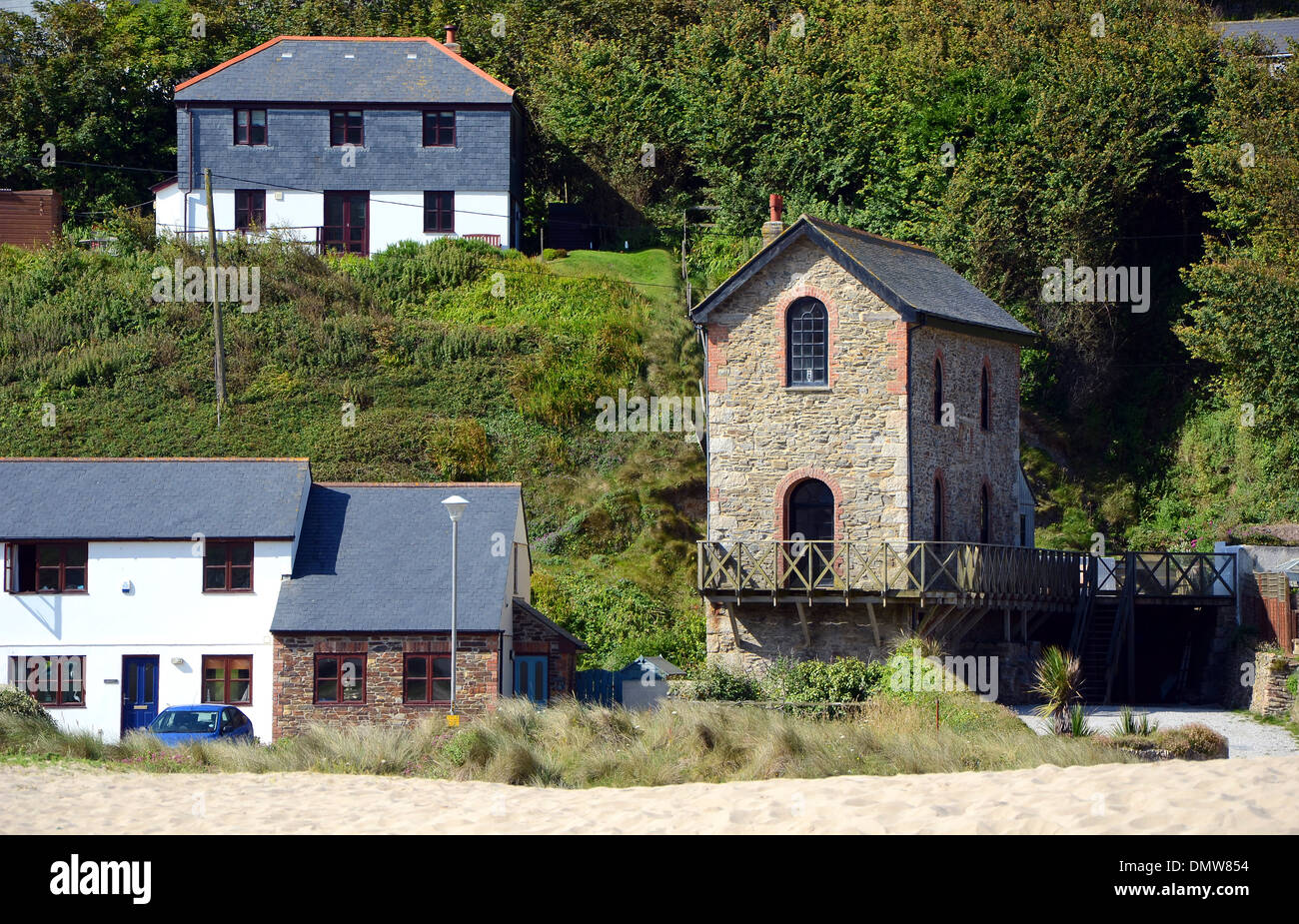 A restored engine house from a former tin mine sits beside new homes at Porthtowan in Cornwall, UK - Stock Image