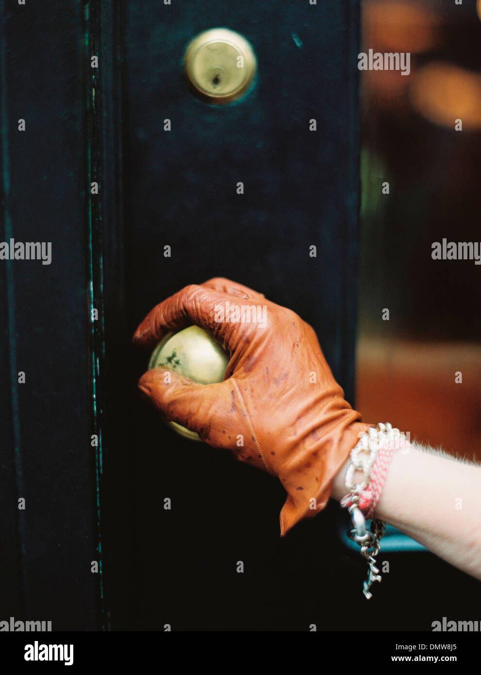 A person wearing a lear glove opening a door. - Stock Image