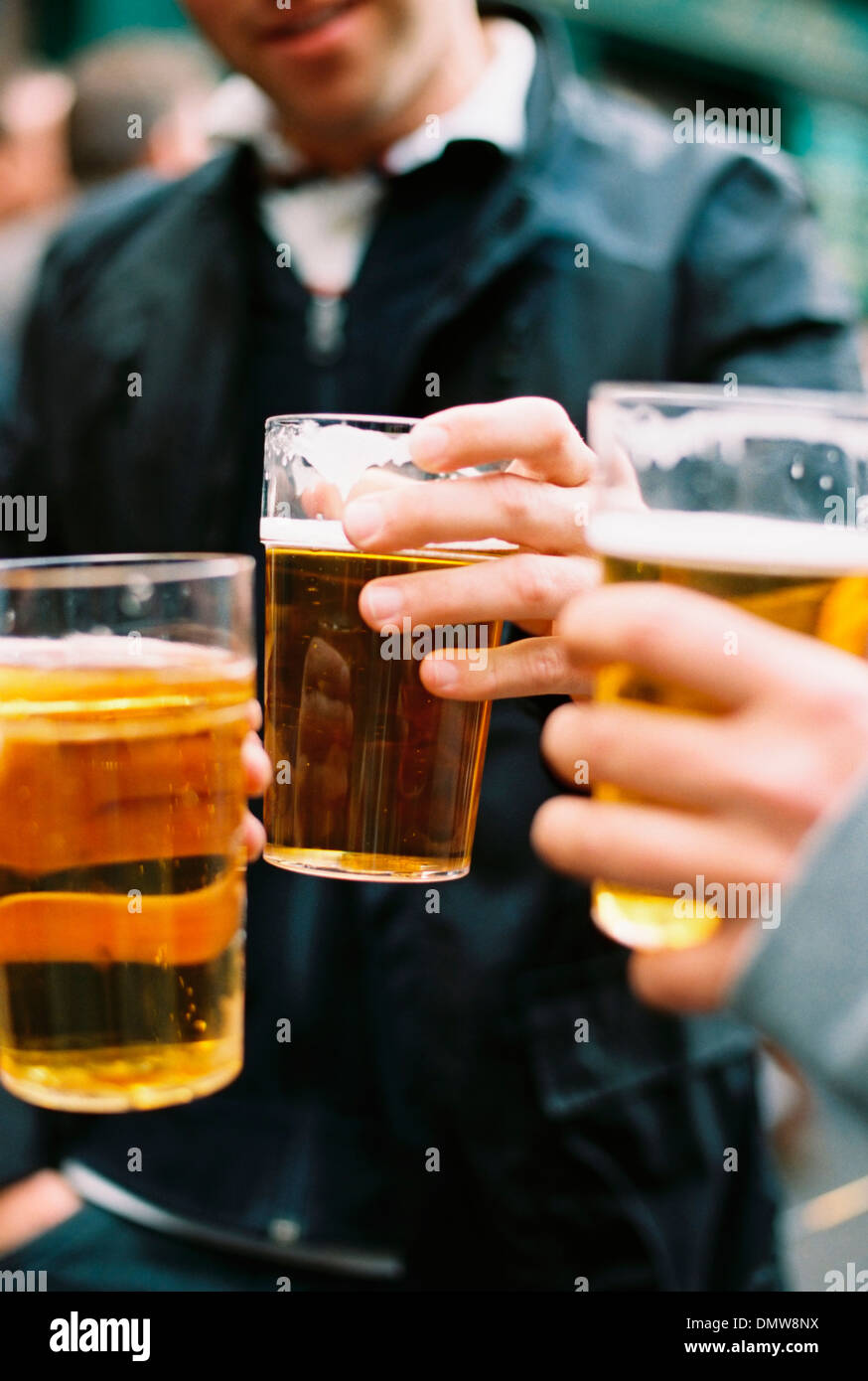 Three people drinking beer. Toasting each or. - Stock Image