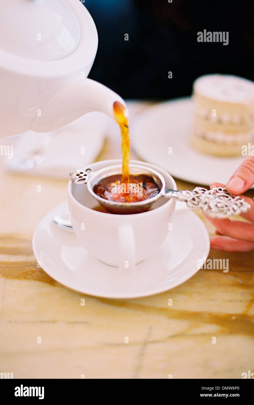 A person pouring a cup of tea using a strainer. White china. Elegant afternoon tea. Stock Photo