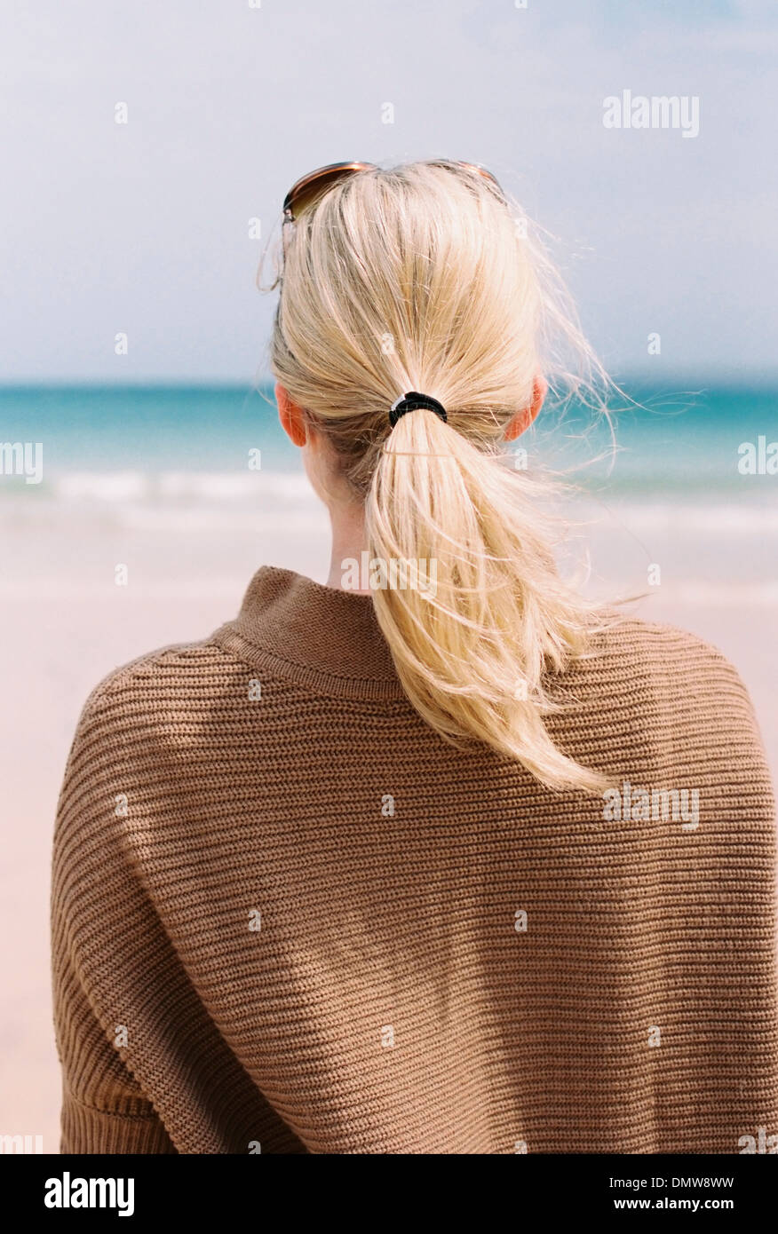 A blonde haired woman looking out to sea from  shore. - Stock Image