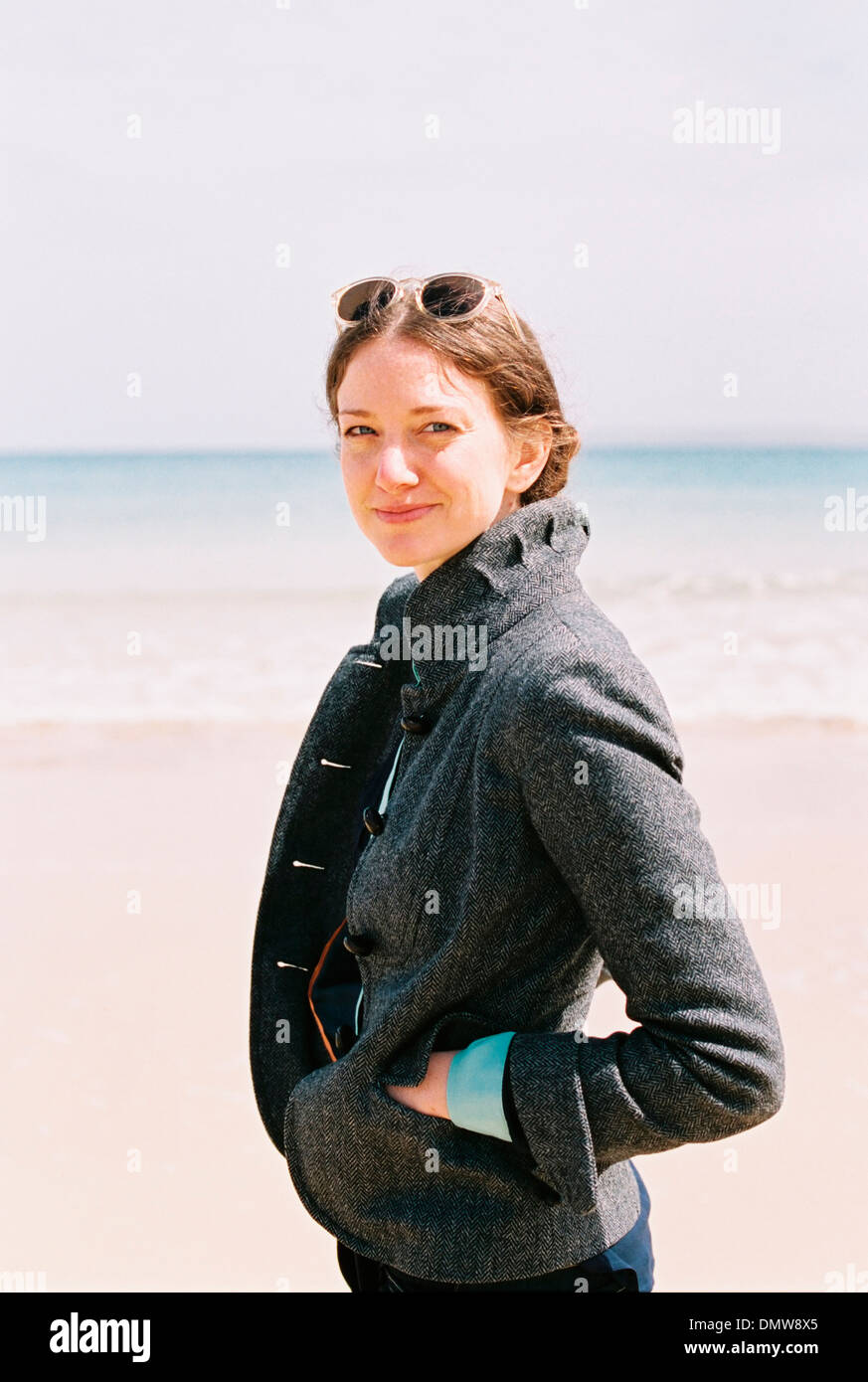 A woman in a grey coat on  beach. - Stock Image