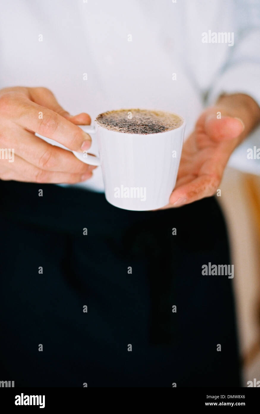 A person holding a full cup of coffee. Froth. - Stock Image