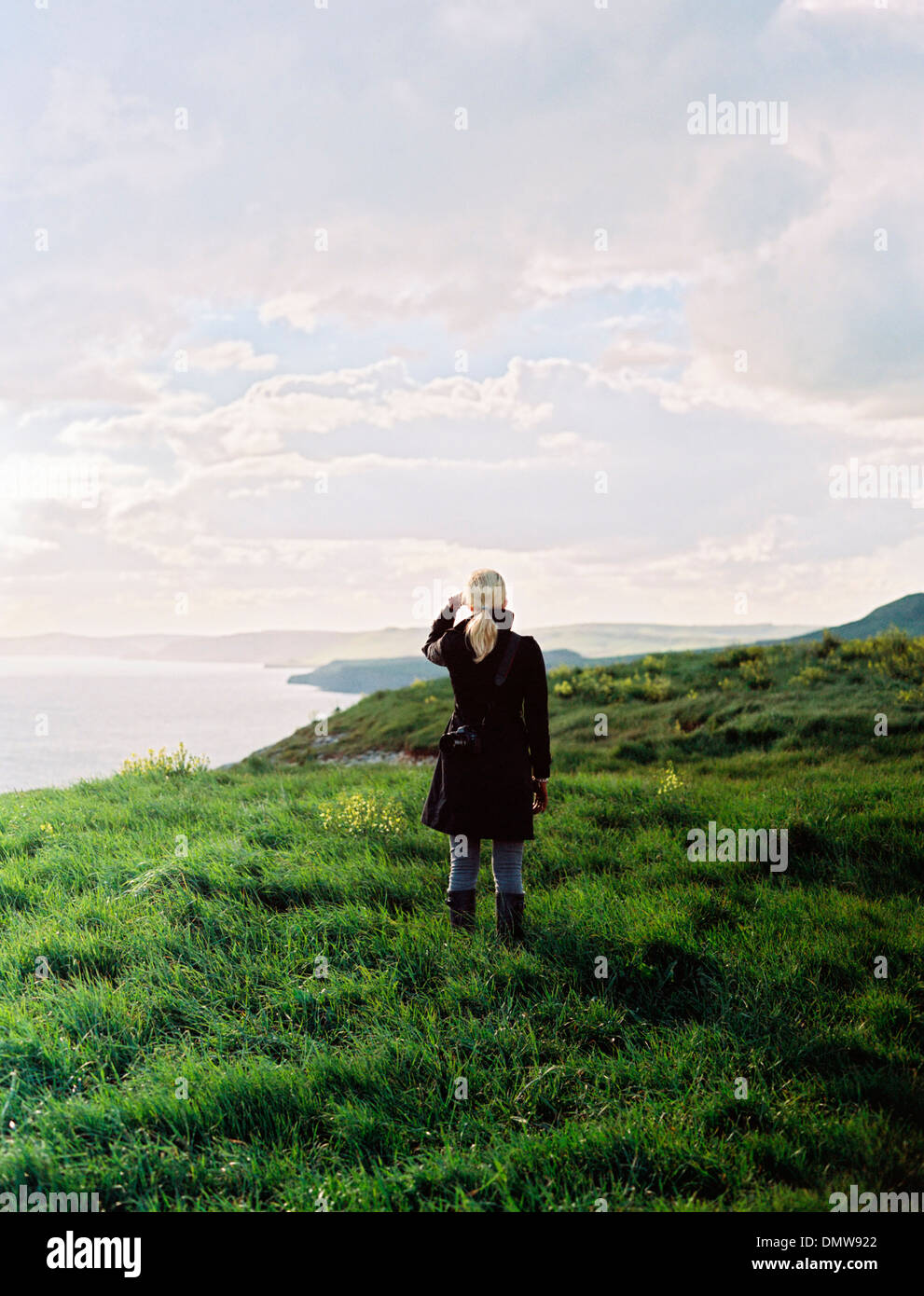 A woman looking along  coastline inlets and cliffs. - Stock Image