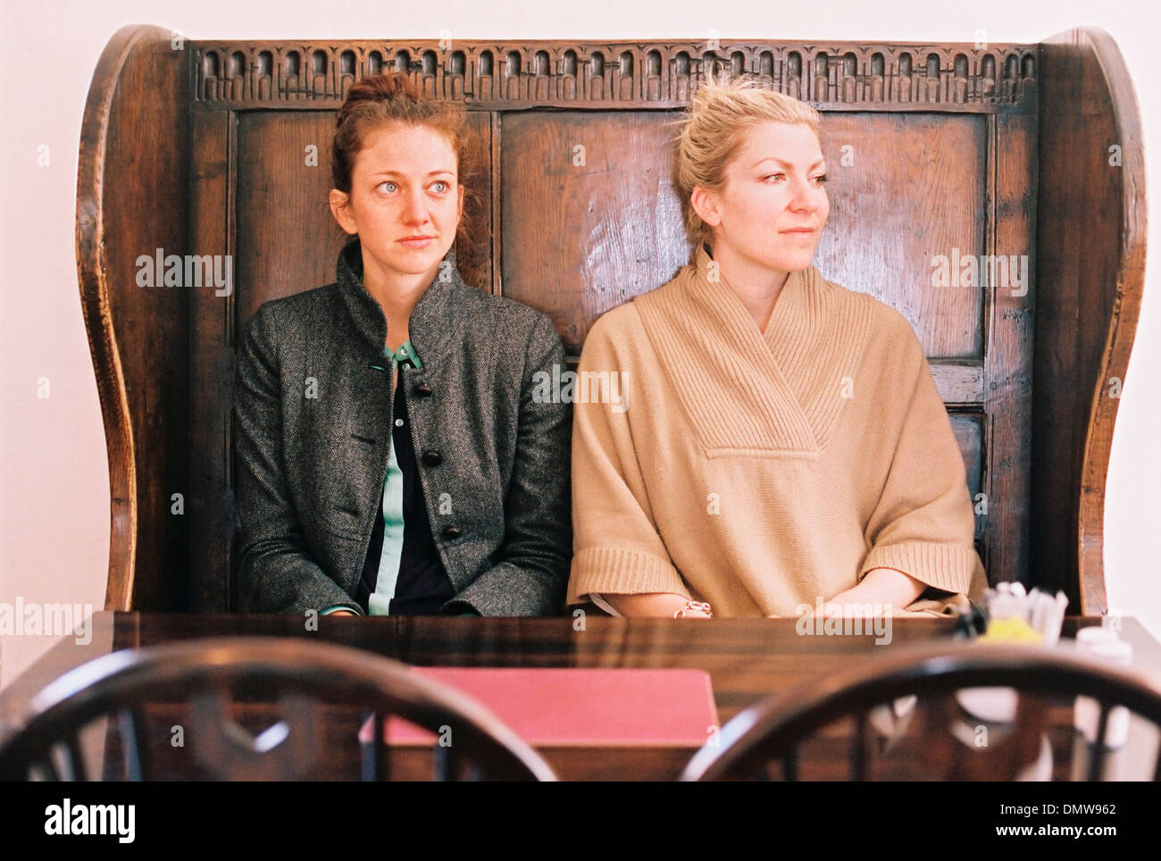 Traditional pub seat with a high back and curved sides. Two women sitting at a table. - Stock Image