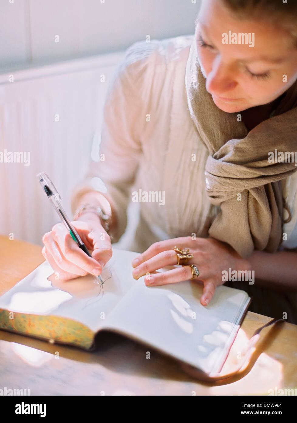 A woman using a coloured pen drawing on a blank page of a diary. - Stock Image