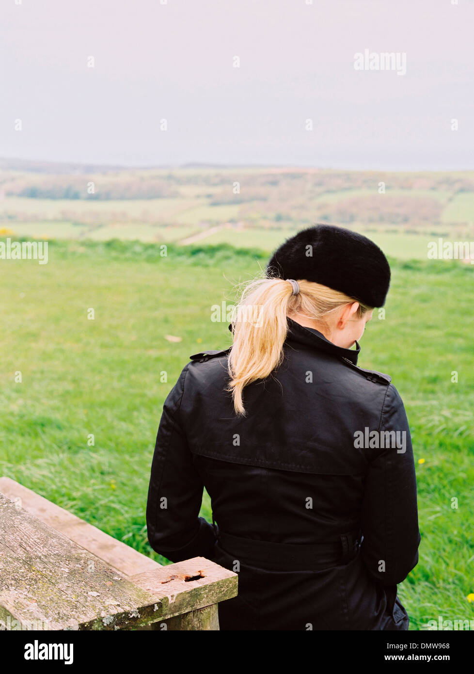 A woman seated on a bench looking over  landscape to  sea. - Stock Image