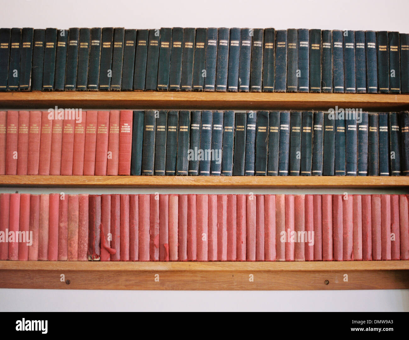 Old books on a shelf. Traditional church prayer books. Worn covers. - Stock Image