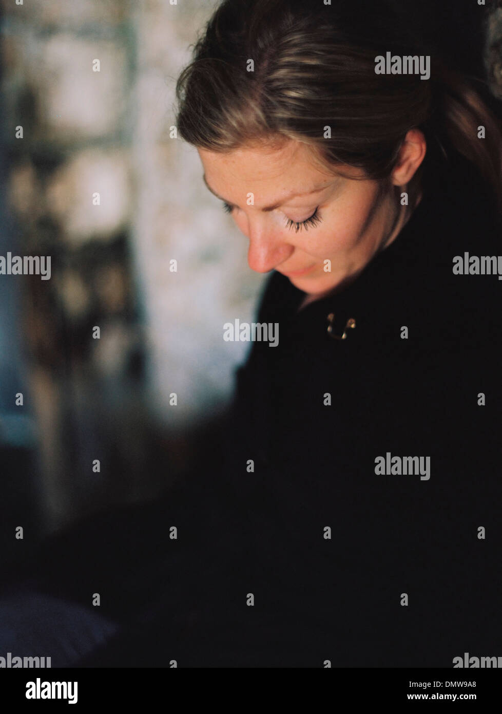 A woman wearing a black coat looking down in a pensive mood. Stock Photo