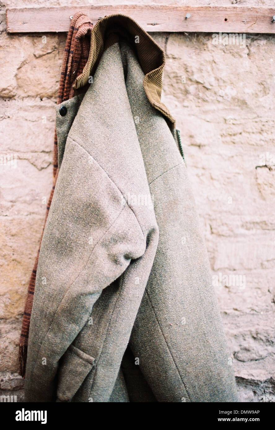 A traditional warm jacket with corduroy collar hanging from a pen on a stone wall. - Stock Image