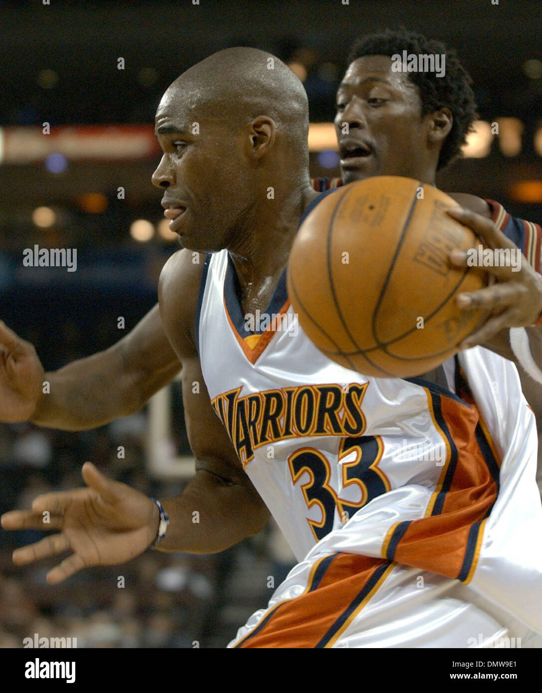 Dec 03, 2002; Oakland, CA, USA;Golden State Warriors Antawn Jamison forces his way down the baseline past Denver Nuggets Donnell Harvey, cq, in the first half of game played at The Arena in Oakland, Calif. on Tuesday December 03, 2002. Jamison scored 22 points in the first half. - Stock Image