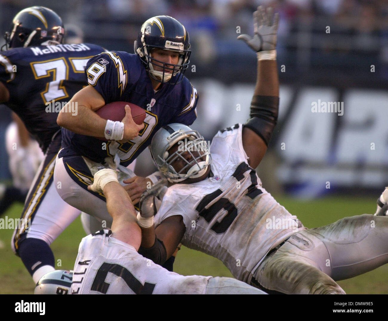 Dec 08, 2002; San Diego, CA, USA; Oakland Raiders' (bottom) John Parrella, #97, and (right) Rod Coleman, #57, sack San Diego Chargers' quarterback Drew Brees, #9, in the 3rd quarter of their game on Sunday, December 8, 2002 at Qualcomm Stadium in San Diego, Calif. Oakland beat San Diego 27-7. - Stock Image