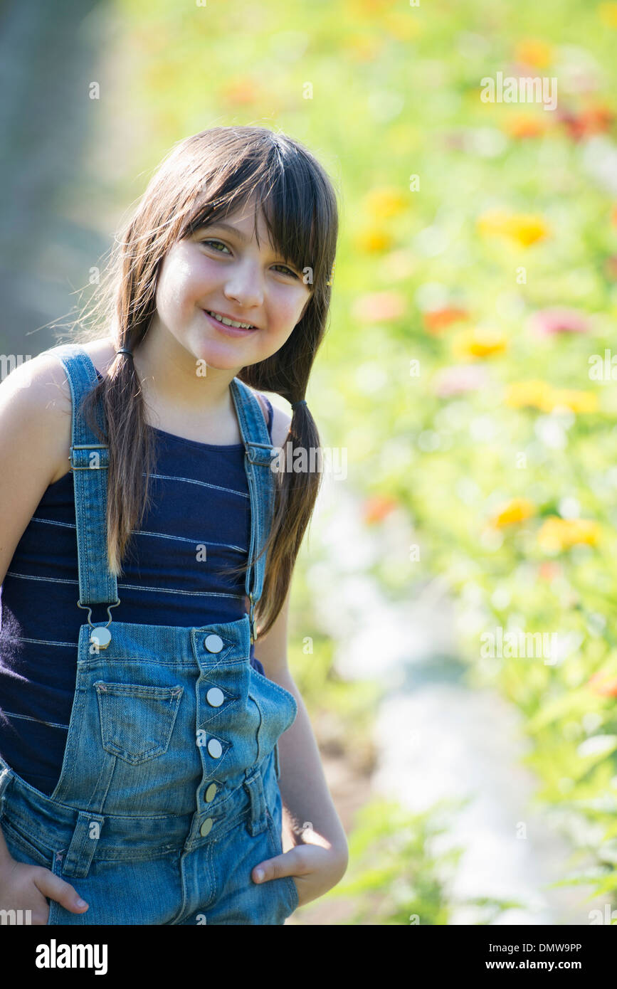 Summer on an organic farm. A young girl in a field of flowers. - Stock Image