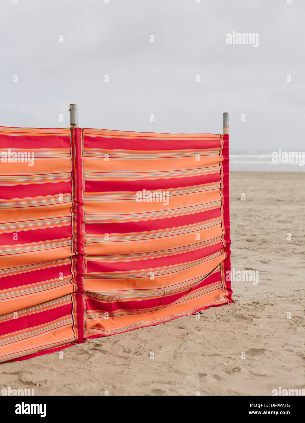 A red striped windbreak on Cannon Beach on  Oregon coast. - Stock Image